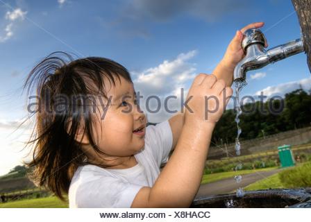 Cute Asian les enfants se laver les mains en parc. Banque D'Images