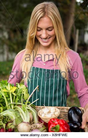 Jardinier heureux avec des légumes frais dans le panier au jardin Banque D'Images