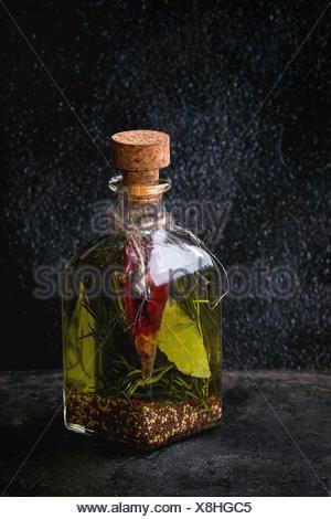 Bouteille de verre d'huile d'olive épicée au romarin, Red Hot Chili Peppers et le laurier sur fond texturé noir permanent. Medit Banque D'Images