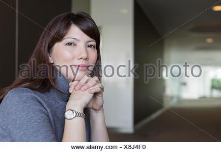 Portrait confident businesswoman with hands clasped Banque D'Images