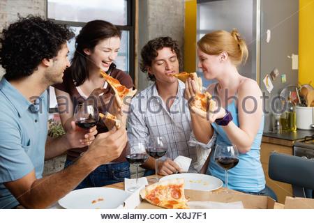 Partage d'une pizza à la maison d'amis Banque D'Images