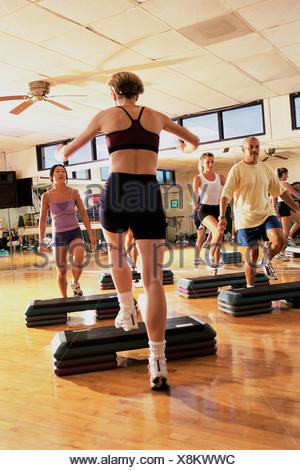 Groupe de personnes exerçant dans une step aerobics class Banque D'Images