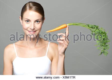 Young woman balancing carotte au bout du doigt Banque D'Images
