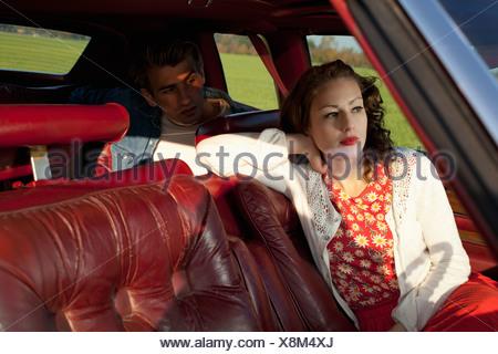 Une femme rockabilly et homme assis dans une voiture ancienne Banque D'Images