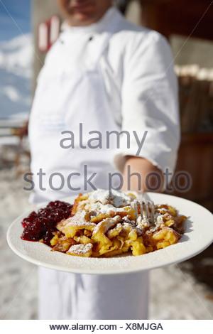Offrant une assiette de nourriture Chef Banque D'Images