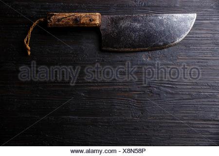 Vintage Boucher couperet à viande couteau sur fond de bois brûlé foncé copy space Banque D'Images