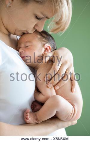 Bébé nouveau-né garçon endormi dans les bras de mère Banque D'Images