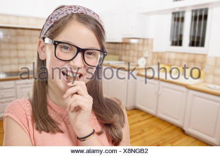 Adorable preteen girl avec des lunettes mange le chocolat, l'arrière-plan de cuisine Banque D'Images