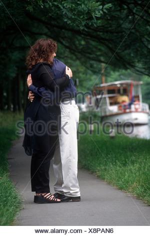 Embrasser femme homme triste à l'extérieur dans le parc, pleine longueur. Banque D'Images