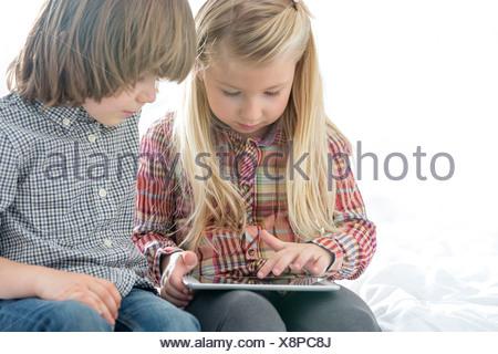 Frère et soeur à l'aide de Tablet PC dans la chambre Banque D'Images