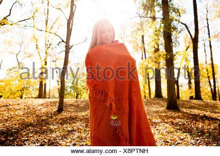 Portrait of young woman wrapped in blanket en forêt d'automne Banque D'Images
