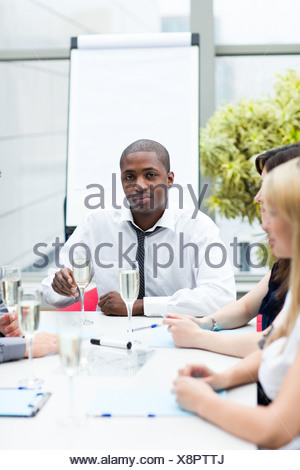 Libre businessman drinking champagne in office Banque D'Images