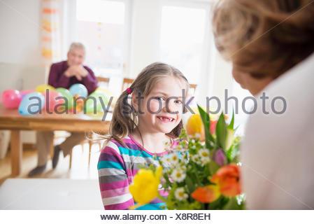 Petite-fille main sur bouquet de fleurs à sa grand-mère tandis que grand-père en arrière-plan Banque D'Images