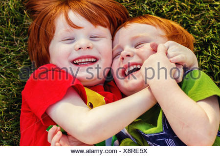 Deux heureux garçons couchés sur l'herbe en riant Banque D'Images