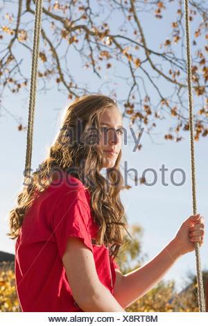 La Suède, Sodermanland, Stigtomta, Teenage girl (14-15) sitting on tree swing dans la lumière du soleil Banque D'Images