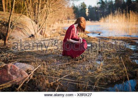 La Finlande, jeune femme World, accroupi dans les zones humides Banque D'Images