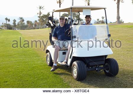 Portrait de deux golfeurs masculins en voiturette de golf