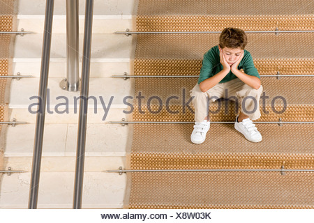 Bored boy on stairway Banque D'Images
