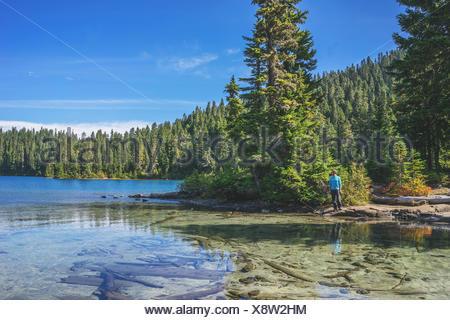 Homme debout par Mountain Lake Banque D'Images