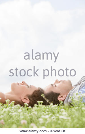 Vue latérale du couple sur l'herbe contre le ciel Banque D'Images