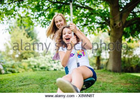 Entre deux filles swinging sur garden swing corde Banque D'Images