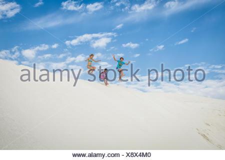 Garçon et deux jeunes filles sautant dans les dunes de sable, tête verte, Australie occidentale, Australie Banque D'Images