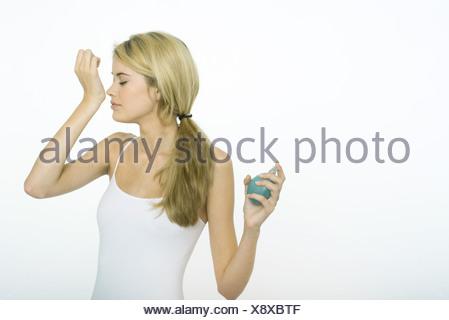 Adolescentes fonctionnant ensemble dans domaine · Teenage girl holding  flacon de parfum, odeur de poignet Banque D Images bce4f973603c