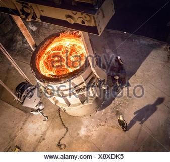 Les travailleurs de l'acier l'inspection de l'acier en fusion dans la fiole, high angle view Banque D'Images