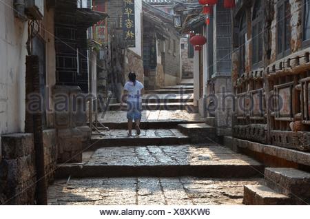 Ruelle, femme marche de larges marches de pierre entre maisons traditionnelles, des minorités Naxi, Lijiang, Yunnan, sud-ouest de la Chine, Chine Banque D'Images