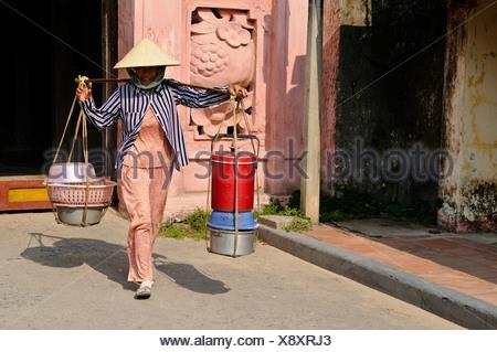 Femme transportant des marchandises contre le pont japonais, Hoi An, Vietnam, Southeast Asia Banque D'Images