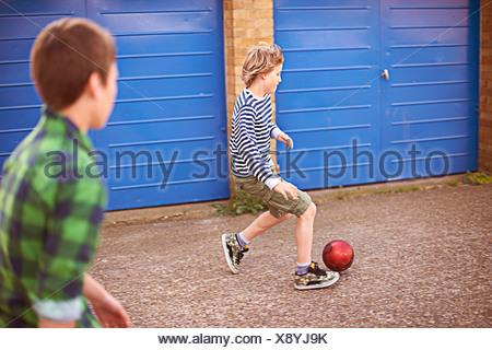 Deux garçons jouant au football par garage Banque D'Images