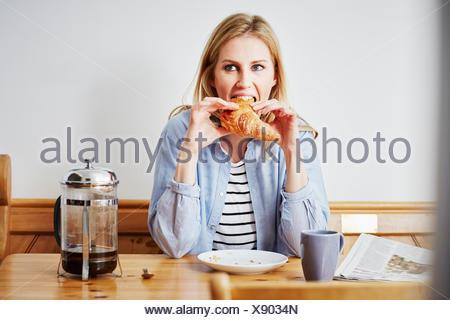 Mid adult woman eating croissant Banque D'Images