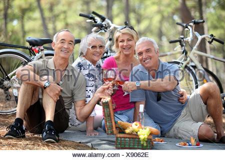 Deux couples plus âgés bénéficiant d''un pique-nique dans les bois Banque D'Images
