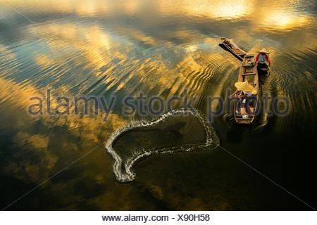 Deux pêcheurs qui jetaient un filet dans la rivière au lever du soleil, Thaïlande Banque D'Images