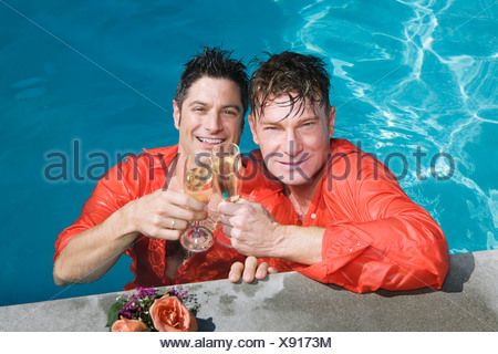 Entièrement vêtu gay couple drinking champagne in swimming pool Banque D'Images