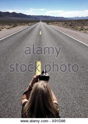 Femme prenant la photo de la route vide, Californie, États-Unis Banque D'Images