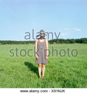 La Finlande, Uusimaa, Lapinjarvi, young woman wearing hat standing on grass Banque D'Images