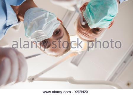 Dentiste et l'assistant se penche au patient Banque D'Images