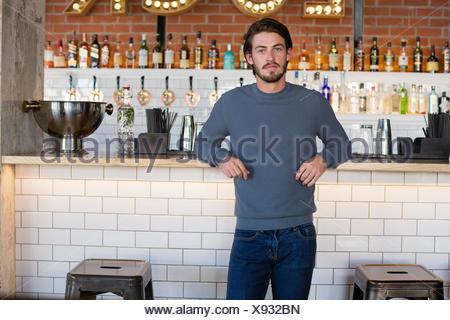 Portrait d'un jeune homme debout au comptoir du bar Banque D'Images