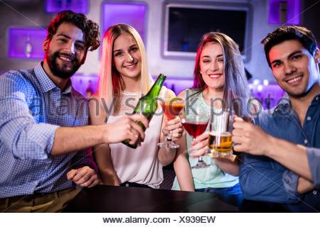 Groupe d'amis toasting Cocktails, bière bouteille et verre de bière au comptoir du bar Banque D'Images