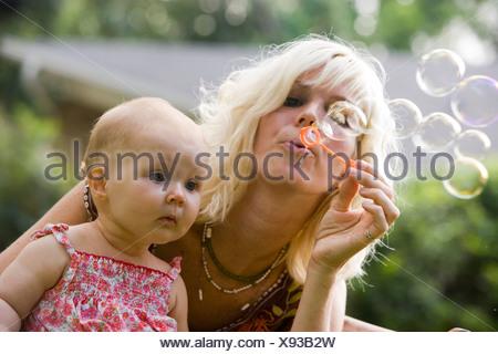 Close-up of mother faisant des bulles avec bébé à la Banque D'Images