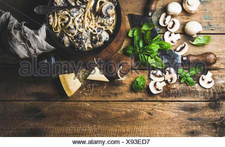 Dîner de style italien. Pâtes aux champignons crémeux spaghettis dans poêle en fonte avec le parmesan, le basilic et le poivre plus vieux rus Banque D'Images