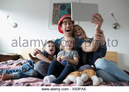 Jeune famille en tenant avec selfies digital tablet on bed Banque D'Images