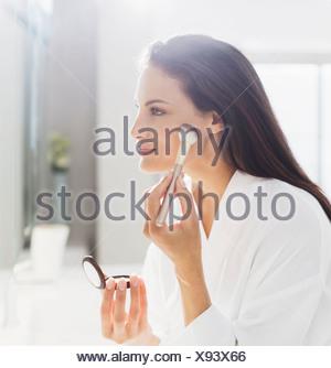Femme en peignoir appliquant le maquillage dans la salle de bains Banque D'Images