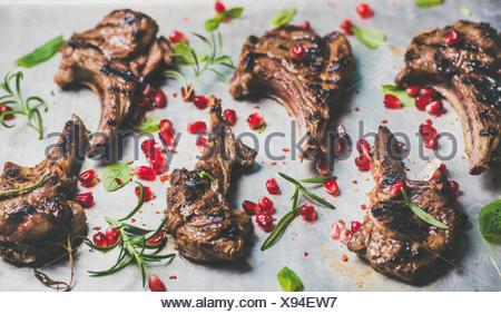 Côtes d'agneau grillées avec graines de grenade, de la menthe et romarin sur plaque de métal background, selective focus, composition horizontale. Bar à viande Banque D'Images