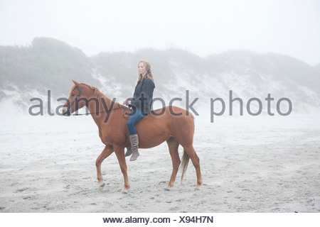 Woman riding horse on beach Banque D'Images