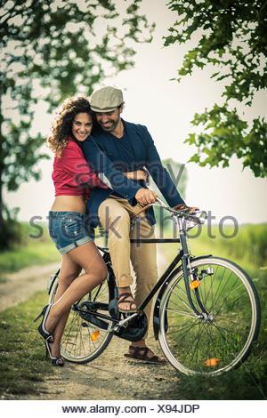 Couple heureux s'amuser tout en bicyclette sur une route de campagne Banque D'Images