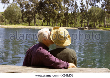 Senior couple kissing par pond Banque D'Images