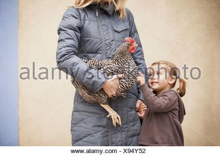 Une femme dans un manteau gris holding chicken with a red coxcomb sous un bras. Une jeune fille à côté d'elle tenant son autre main Banque D'Images