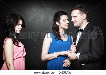 L'infidélité conjugale concept. Triangle d'amour deux femmes un homme la passion de l'amour de la haine. Mistress trahison au sein de la famille. Fond noir Banque D'Images